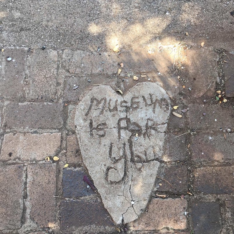 Paving stones with a heart shaped section which has the words Museum is for you etched into it.